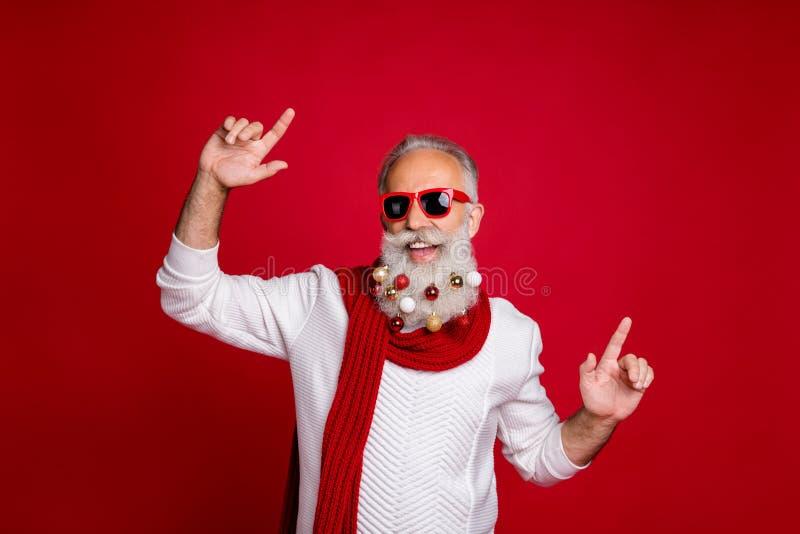 Ritratto di un pensionato allegro con occhiali da sole che ballano indossando un pullover bianco isolato su fondo rosso immagini stock