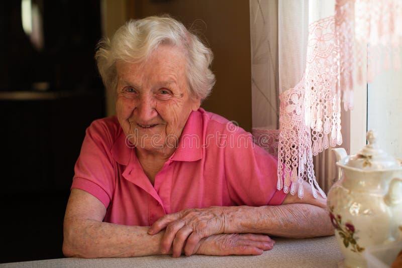 Ritratto di un pensionato anziano della donna che si siede ad una tavola nella cucina nella sua casa immagine stock