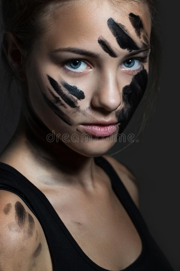 Ritratto di un primo piano della ragazza Fronte spalmato di pittura nera immagini stock