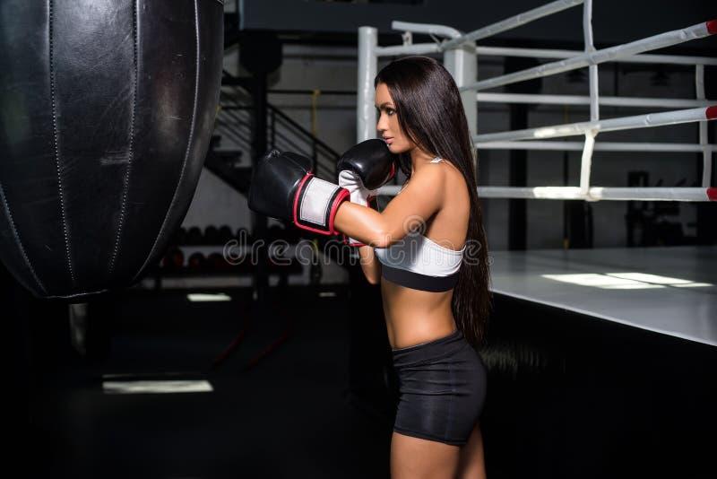 Ritratto di un pugile della donna, aggressivo e pronto a combattere Perforazione del punching ball fotografia stock