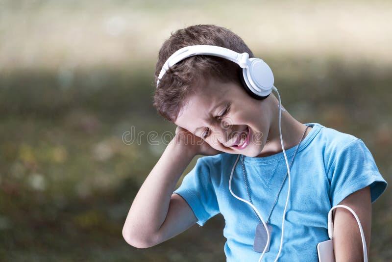 Ritratto di un ragazzino dolce che ascolta la musica fotografia stock libera da diritti