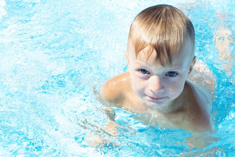 Ritratto di un ragazzino sveglio che nuota nello stagno fotografia stock