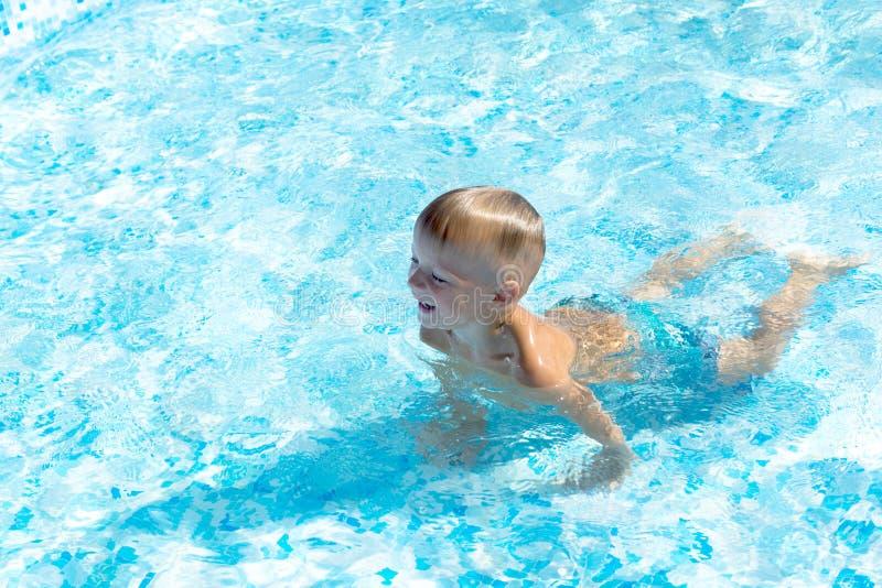 Ritratto di un ragazzino sveglio che nuota nello stagno fotografia stock libera da diritti