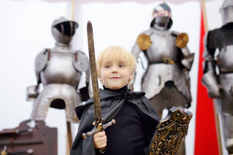 Ritratto di un ragazzino sveglio vestito come cavaliere medievale con una spada e uno schermo su fondo dell'armatura del cavalier immagini stock libere da diritti