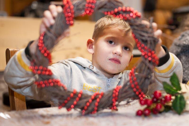 Ritratto di un ragazzo con una corona di Natale decorata con le perle rosse fotografia stock libera da diritti