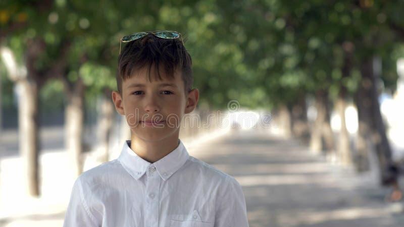 Ritratto di un ragazzo divertente che esamina la macchina fotografica sulla via fotografia stock libera da diritti