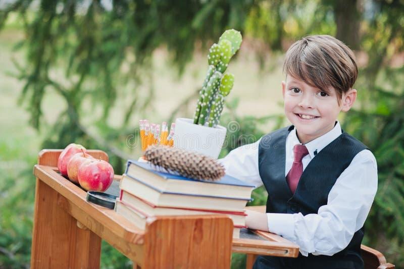 Ritratto di un ragazzo smily del primo selezionatore che si siede ad uno scrittorio fotografie stock libere da diritti