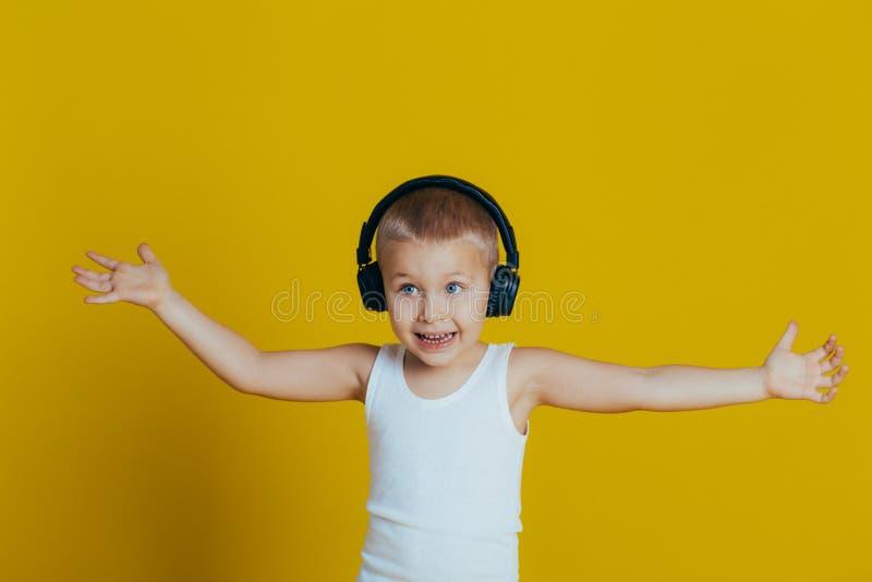 Ritratto di un ragazzo sorridente attraente in una maglietta bianca che ascolta la musica attraverso il primo piano delle cuffie fotografia stock