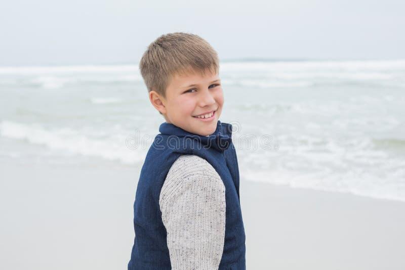 Ritratto di un ragazzo sorridente sveglio alla spiaggia fotografia stock