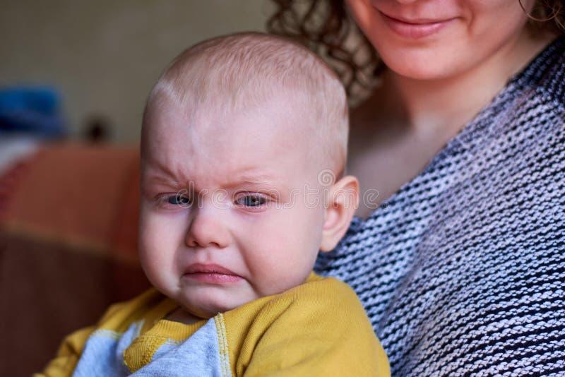 Ritratto di un ragazzo triste che fa smorfie vicino a sua madre, manifestazione di malcontento del bambino fotografia stock
