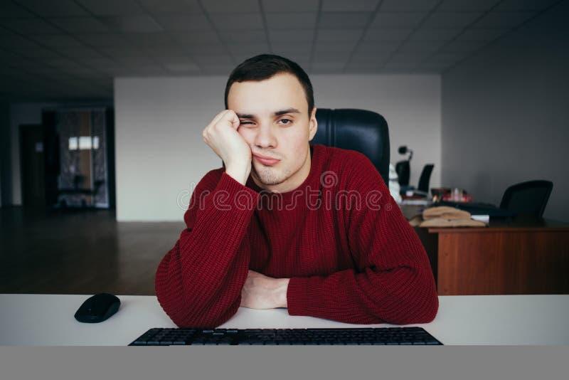 Ritratto di un ` s del giovane stanco con il computer Contro lo sfondo di spazio ufficio La situazione nell'ufficio fotografia stock libera da diritti