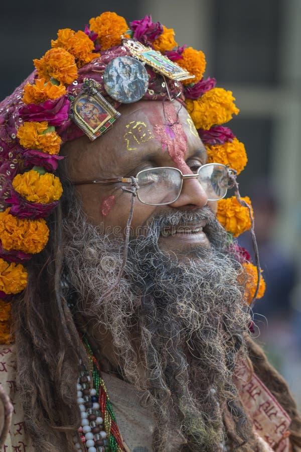 Ritratto di un Sadhu con il copricapo unico fatto dai fiori a Barsana, Uttar Pradesh, India fotografia stock