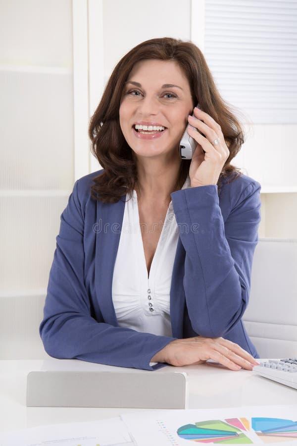 Ritratto di un senior manager femminile che chiama allo scrittorio immagini stock libere da diritti