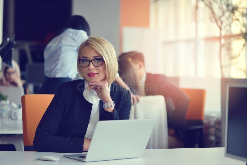 Ritratto di un socio commerciale femminile biondo nel suo 30 ` s che si siede al suo scrittorio ordinato davanti al suo computer fotografia stock libera da diritti