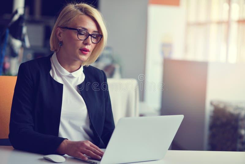 Ritratto di un socio commerciale femminile biondo nel suo 30 ` s che si siede al suo scrittorio ordinato davanti al suo computer immagini stock
