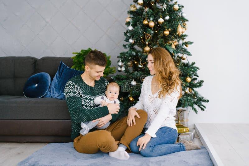 Ritratto di un sorridere felice e famiglia allegra nel salone, decorati per il Natale immagini stock