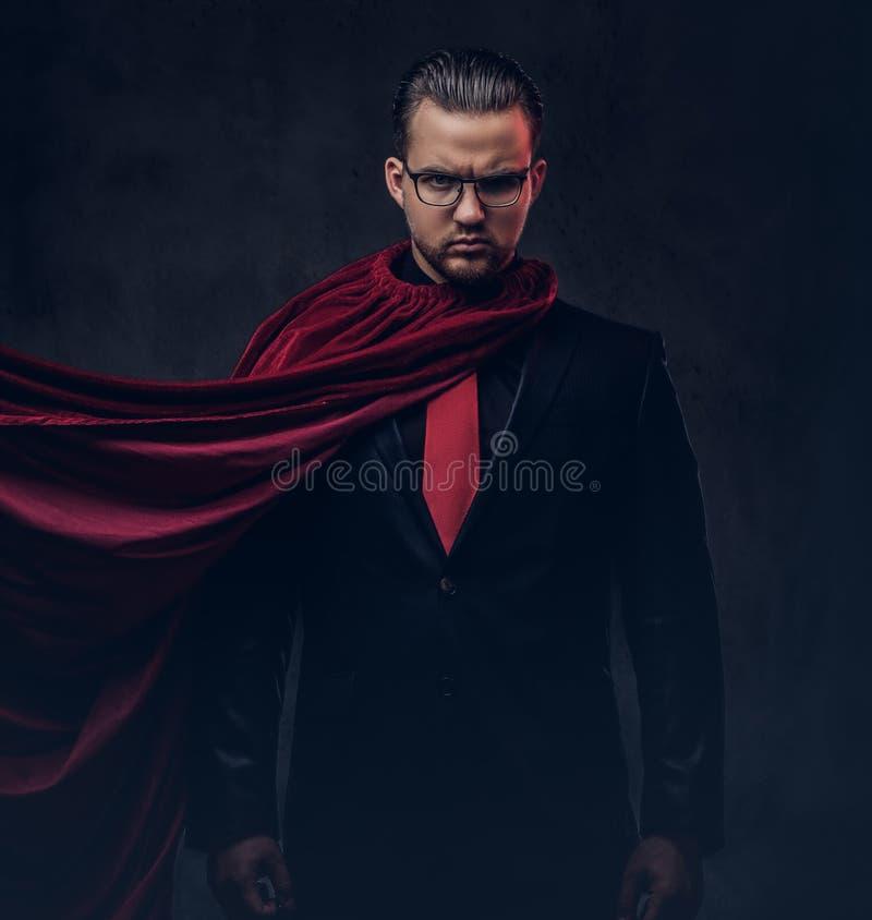 Ritratto di un supereroe del genio in un vestito nero con un legame rosso su un fondo scuro immagine stock libera da diritti