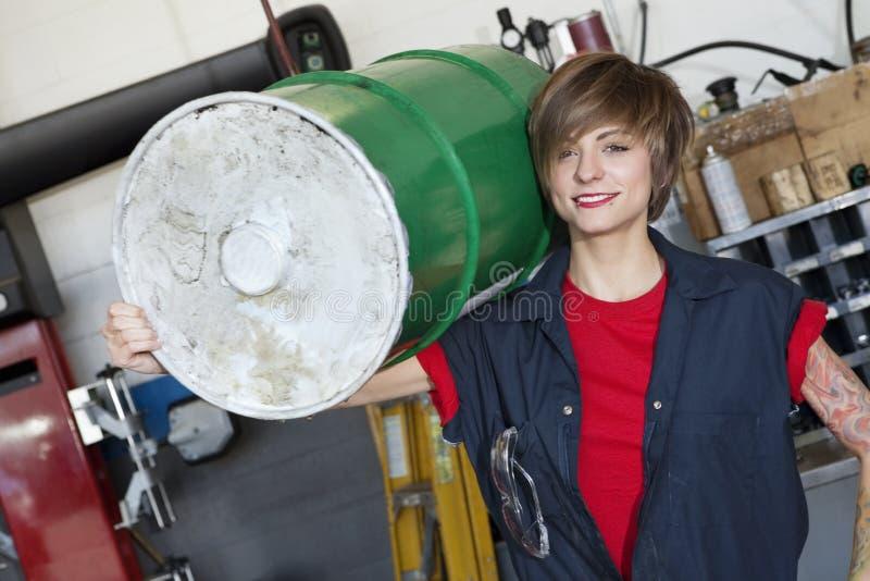 Ritratto di un tamburo dell'olio di trasporto del giovane meccanico femminile felice sulla spalla nell'officina dell'automobile immagini stock libere da diritti