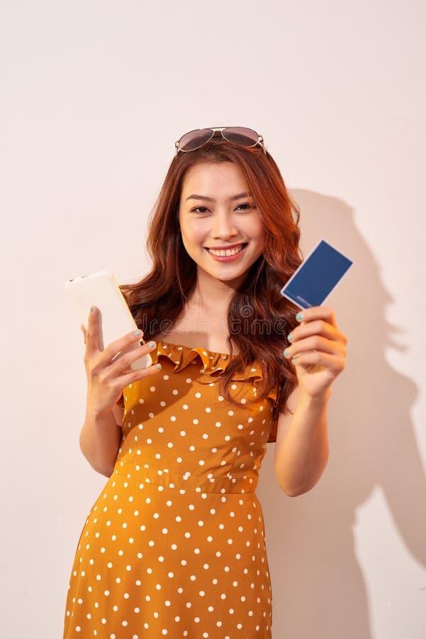 Ritratto di un telefono cellulare felice della tenuta della ragazza e di una carta di credito isolati sopra il fondo del biege fotografia stock