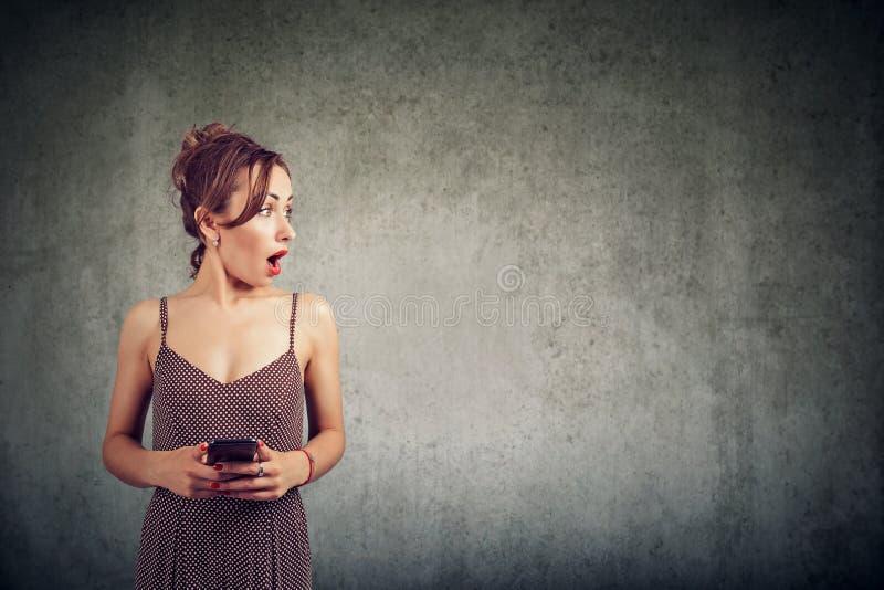 Ritratto di un telefono cellulare sorpreso e di distogliere lo sguardo della tenuta della donna lo spazio della copia immagine stock