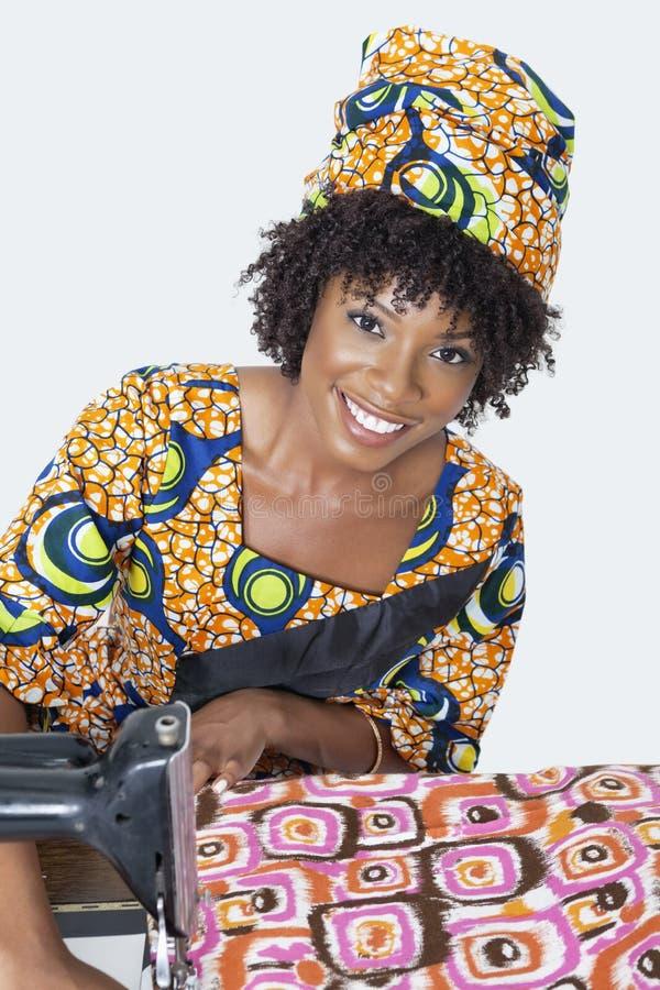 Ritratto di un tessuto di cucito dello stilista femminile afroamericano sopra fondo grigio immagine stock libera da diritti