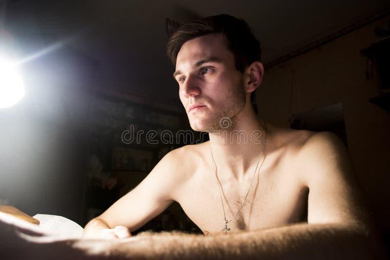 Ritratto di un tipo bello con un torso nudo Foto di un primo piano in una stanza scura e di una luce da una lampada Indicatore lu immagine stock libera da diritti