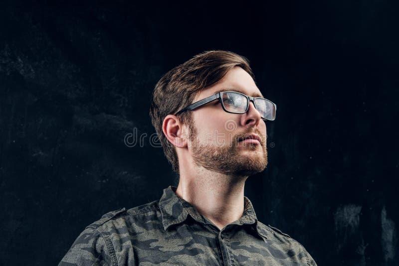 Ritratto di un tipo bello in una camicia militare alla moda che guarda lateralmente Foto dello studio con fondo scuro fotografia stock
