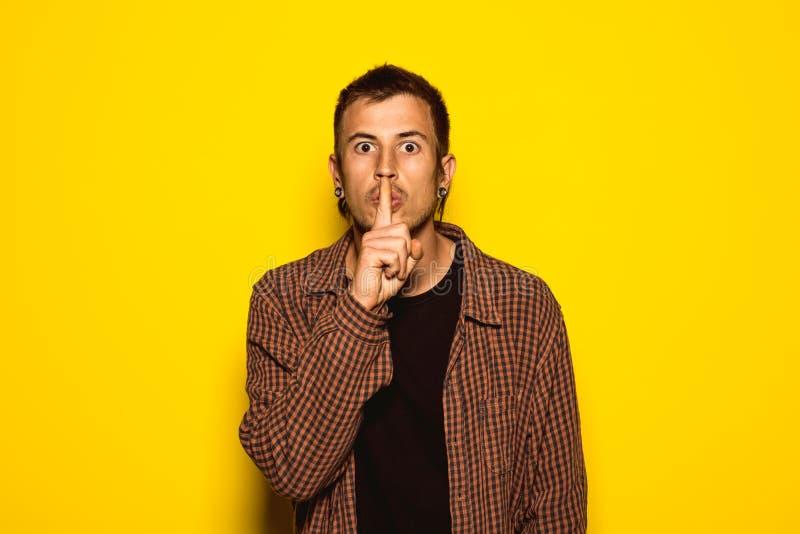 Ritratto di un tipo che fa un gesto silenzioso con la sua mano nella sua bocca fotografie stock libere da diritti