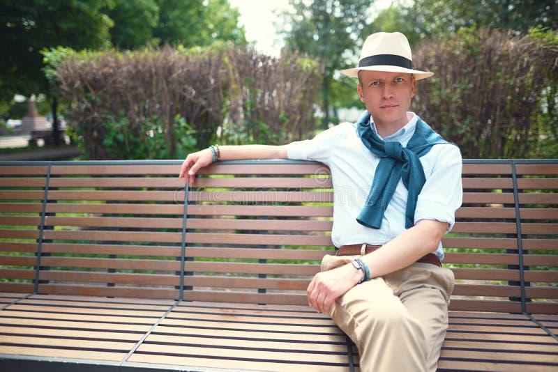 Ritratto di un tipo che si siede su un banco di parco immagini stock libere da diritti