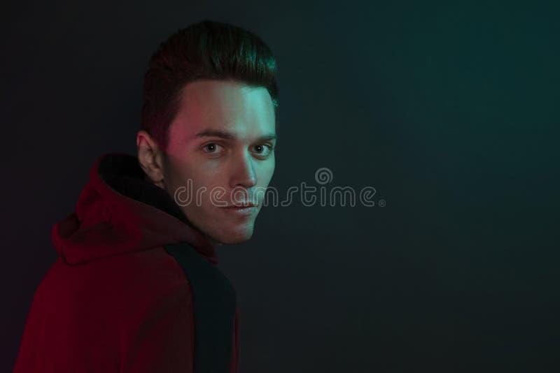 Ritratto di un tipo in un maglione incappucciato su fondo nero nello studio fotografia stock