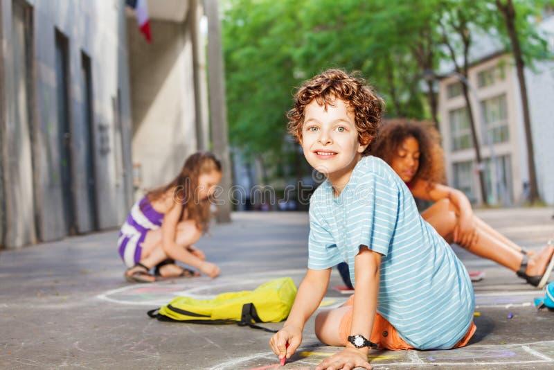 Ritratto di un tiraggio del ragazzo con gli amici sulla via fotografia stock