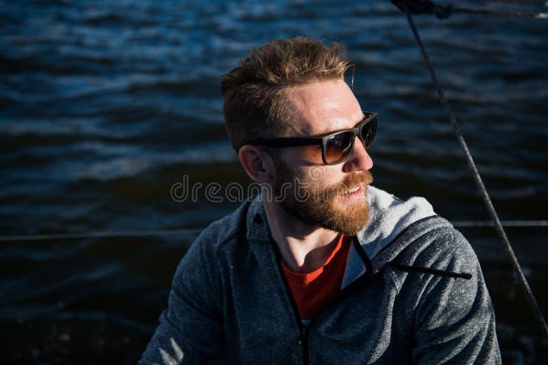 Ritratto di un uomo alla moda del pescatore che conduce un'imbarcazione a motore nel tempo di tramonto immagini stock