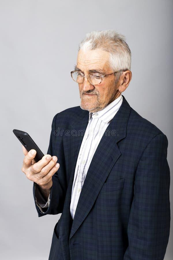 Ritratto di un uomo anziano che per mezzo del telefono di mobil fotografie stock libere da diritti