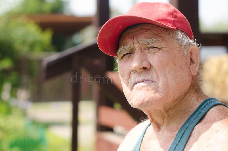 Ritratto di un uomo anziano in un berretto da baseball rosso fotografia stock libera da diritti
