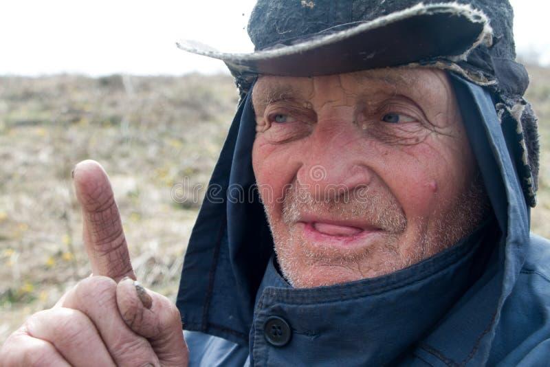 Ritratto di un uomo anziano in vestiti e cappello sudici che hanno alzato il suo dito indice, ho un'idea immagini stock