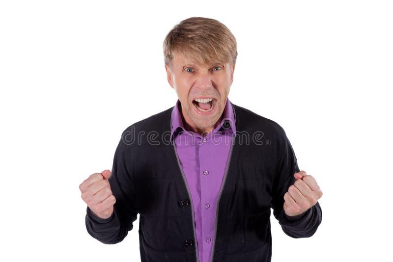 Ritratto di un uomo arrabbiato in grido lilla del cardigan e della camicia e pugni di tenuta su fondo bianco fotografia stock libera da diritti