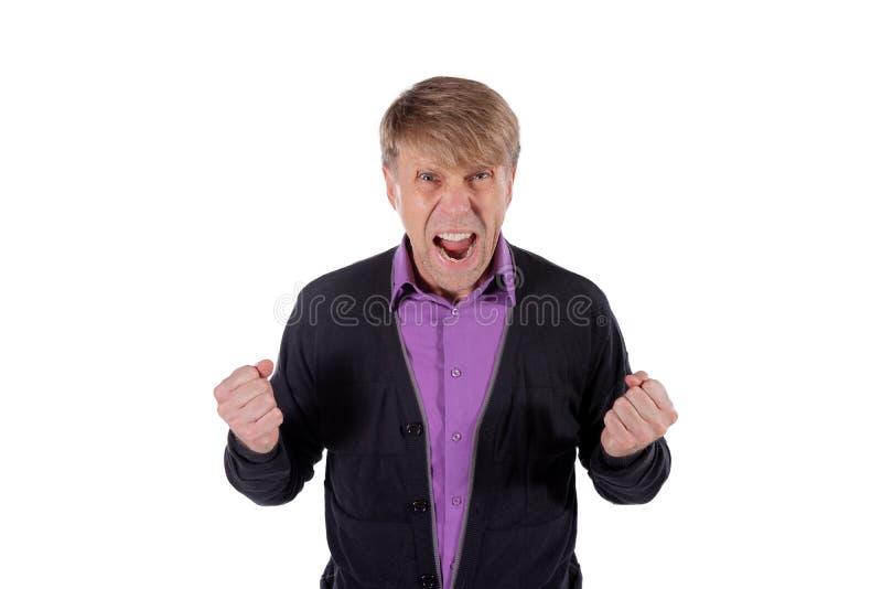 Ritratto di un uomo arrabbiato in grido lilla del cardigan e della camicia e pugni di tenuta su fondo bianco fotografia stock