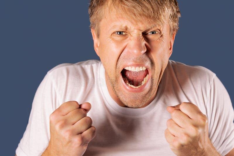 Ritratto di un uomo arrabbiato in maglietta bianca che tiene i pugni su fondo blu fotografia stock libera da diritti