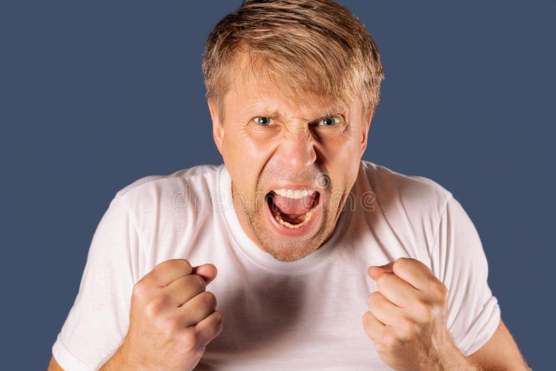 Ritratto di un uomo arrabbiato in maglietta bianca che tiene i pugni su fondo blu immagine stock libera da diritti