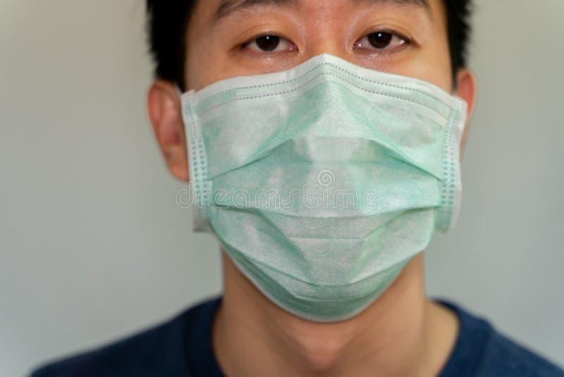 Ritratto di un uomo asiatico con una maschera protettiva contro malattie contagiose e coronavirus immagine stock libera da diritti