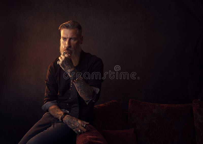 Ritratto di un uomo barbuto attraente di affari che sta sedendosi in una stanza scura che pensa a qualcosa immagini stock