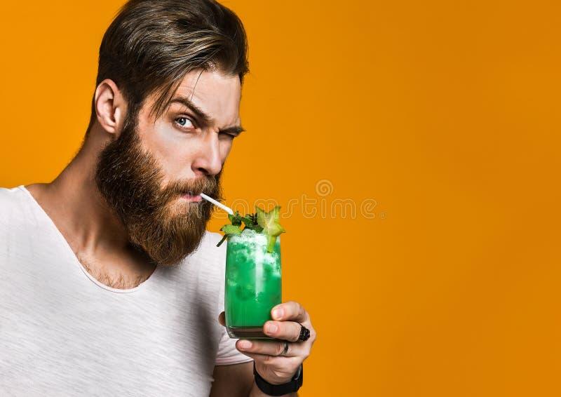 Ritratto di un uomo barbuto carismatico con un cocktail in sue mani fotografia stock libera da diritti