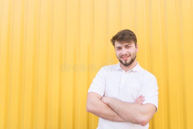 Ritratto di un uomo barbuto vestito in una maglietta bianca sui precedenti di una parete gialla fotografie stock