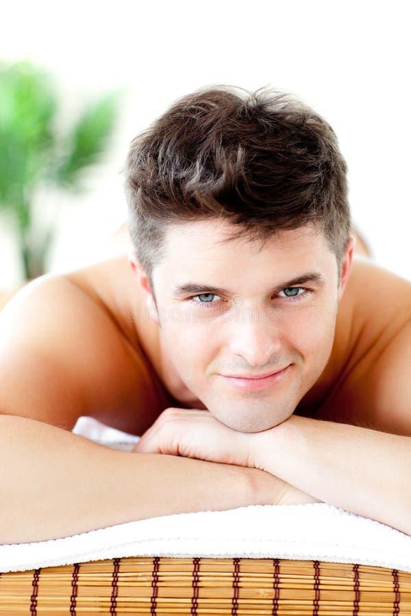Ritratto di un uomo bello che si trova sulla tabella di massaggio fotografia stock