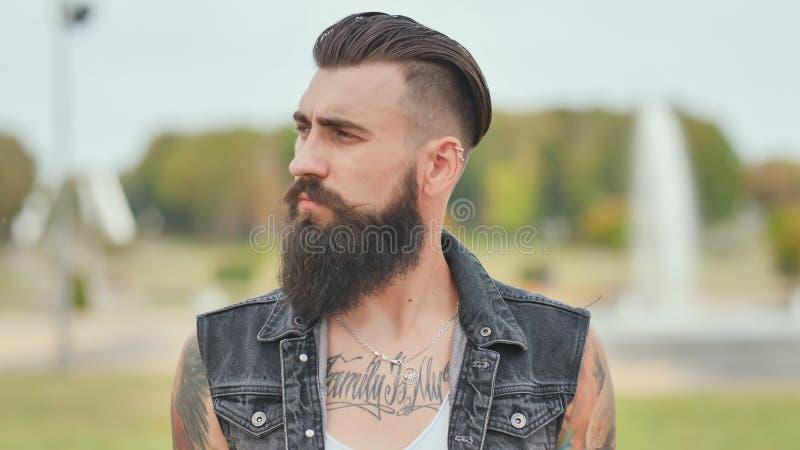 Ritratto di un uomo brutale e barbuto con i tatuaggi sulle sue spalle immagine stock libera da diritti