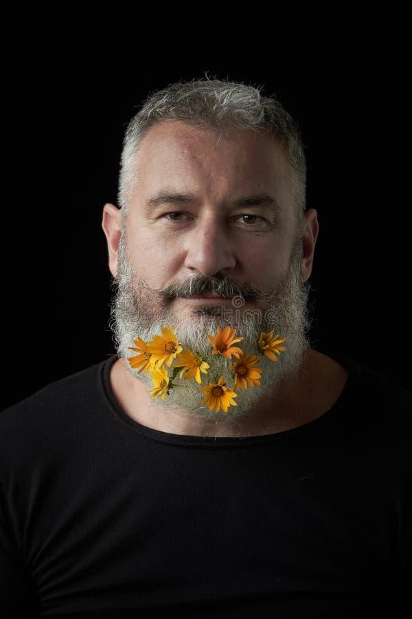 Ritratto di un uomo brutale sorridente con una barba grigia decorata con i fiori gialli su un fondo nero, fuoco selettivo immagini stock libere da diritti