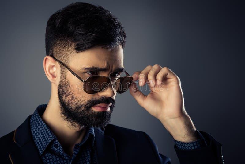 Ritratto di un uomo brutalmente alla moda con giacca e occhiali immagine stock libera da diritti