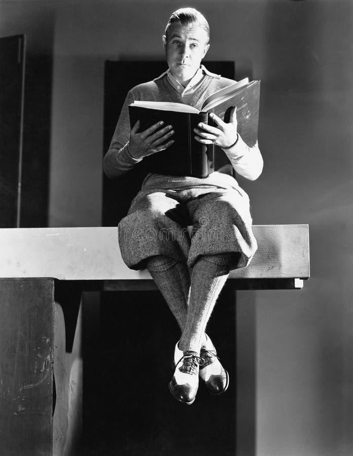 Ritratto di un uomo che si siede su una plancia di legno e che tiene un libro (tutte le persone rappresentate non sono vivente pi immagine stock