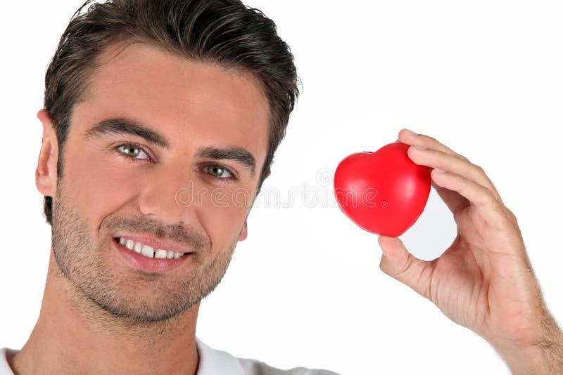 Ritratto di un uomo che tiene un cuore fotografia stock