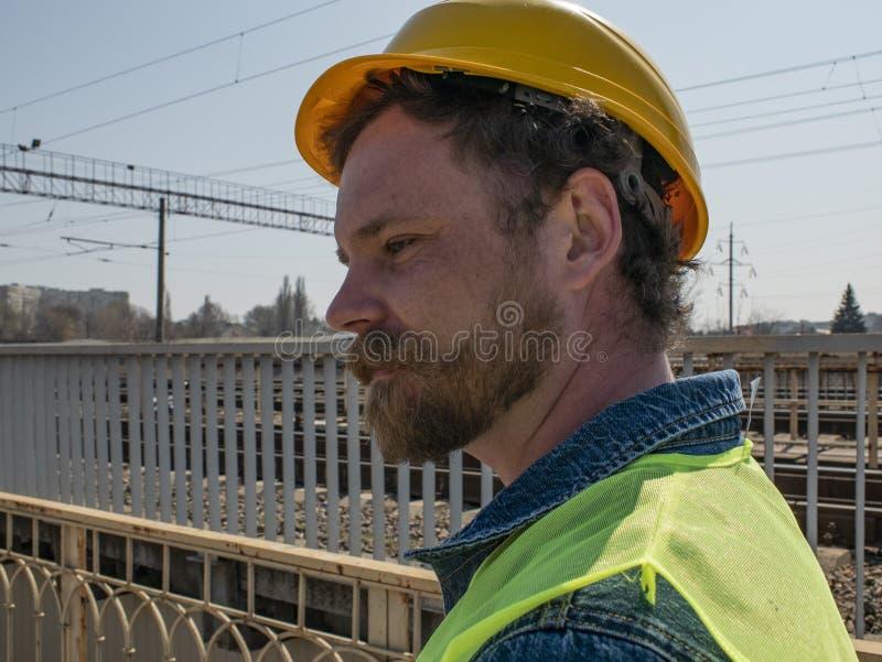 Ritratto di un uomo con una barba e dei baffi in un casco contro lo sfondo della strada ferrata Lavoratore ferroviario immagine stock